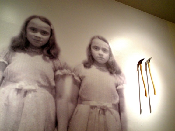 "The image of these girls loomed over the room devoted to ""The Shining"" (where there were also ominous axes in the wall)"