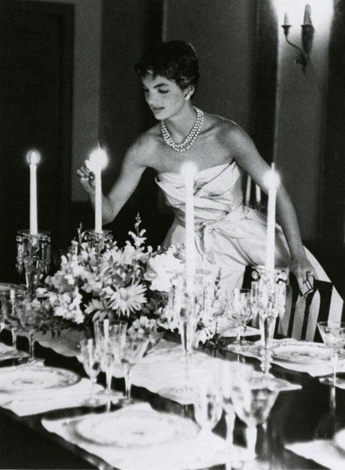 Jackie Kennedy lighting candles in a very glam gown
