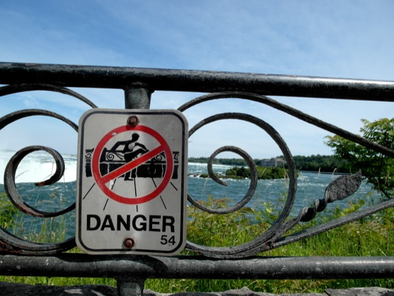 A super-detailed sign warns against the dangers of climbing over the fence that surrounds the falls