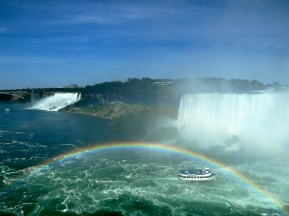 The magestic falls and a rainbow arcing over a tour boat